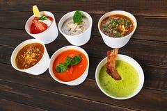 Разнообразие супов от различных кухонь на коричневой древесине Стоковые Фотографии RF