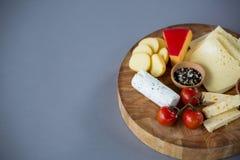 Разнообразие сыра с томатом и специями вишни на деревянной доске Стоковые Изображения