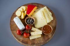 Разнообразие сыра с томатом и специями вишни на деревянной доске Стоковое Фото