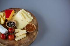 Разнообразие сыра с томатом, соусом и специями вишни на деревянной доске Стоковые Фотографии RF