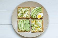 Разнообразие сэндвичей на завтрак, закуска, закуски, авокадо, плавленый сыр на сэндвичах хлеба, белая предпосылка стоковая фотография
