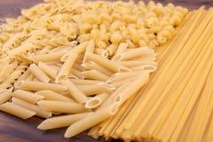 Разнообразие типы и формы итальянских сухих макаронных изделий на деревянной предпосылке Сырые, трудные, сырцовые и сухие макарон стоковое изображение