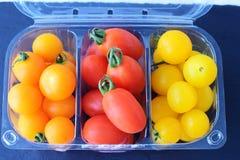Разнообразие томатов вишни Красные, желтые и оранжевые томаты вишни в пластмасовом контейнере на серой абстрактной предпосылке Стоковое Изображение
