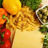 Разнообразие uncooced итальянских макаронных изделий на деревянном столе Стоковое Изображение