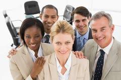 Разнообразная близкая команда дела усмехаясь вверх на камере Стоковая Фотография
