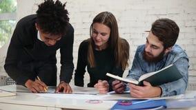 Разнообразная группа людей работая совместно рисующ план, работая на проекте Усмехаясь африканский работник офиса рисуя a видеоматериал