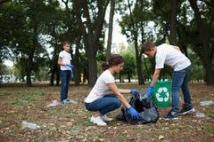 Разнообразная команда группы людей с рециркулирует проект, выбирая вверх погань в социальном обеспечении волонтера парка Стоковое Фото
