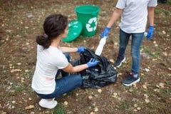 Разнообразная команда группы людей с рециркулирует проект, выбирая вверх погань в социальном обеспечении волонтера парка Стоковые Изображения