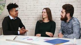 Разнообразная команда дела играя игры в офисе Компания друзей имея потеху в офисе Наклеенное молодые люди сток-видео