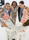 Разнообразная команда дела обнимая в круге усмехаясь на камере Стоковые Фото