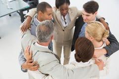 Разнообразная команда дела обнимая в круге Стоковые Изображения