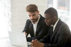 Разнообразные бизнесмены в костюмах анализируя онлайн проект совместно o стоковое фото