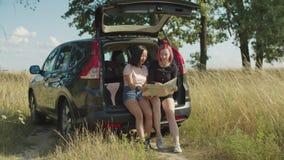 Разнообразные женщины ища положение на карте в багажнике автомобиля акции видеоматериалы