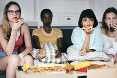 Разнообразные женщины сидя на кресле есть пиццу совместно Стоковые Изображения RF