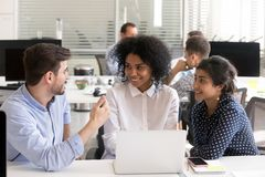 Разнообразные коллеги обсуждая онлайн проект на рабочем месте стоковые изображения
