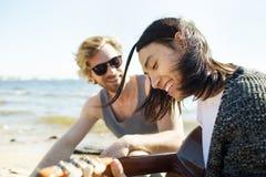 Разнообразные люди играя гитару на пляже Стоковые Изображения