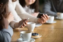 Разнообразные люди используя smartphones на таблице кафа, конце вверх по взгляду Стоковые Фото