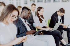 Разнообразные люди работая на мобильных телефонах, корпоративные работники офиса держа смартфоны на встрече Серьезное multiracial стоковые изображения