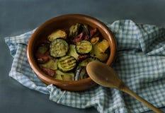 Разнообразные овощи сварили в глиняном горшке, на темноте - серой предпосылке стоковое изображение rf
