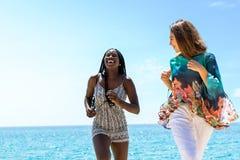 Разнообразные подруги имея большую потеху на пляже Стоковое Фото