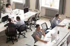 Разнообразные работники офиса используя компьютеры в современном корпоративном космосе стоковое фото rf