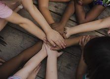 Разнообразные руки соединяют совместно на деревянном столе стоковые фотографии rf