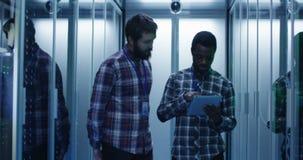 Разнообразные специалисты по ИТ с планшетом в комнате сервера видеоматериал