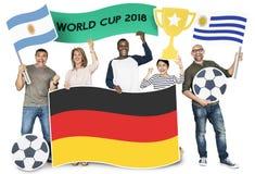 Разнообразные футбольные болельщики держа флаги Аргентины, Германии и Уругвая стоковое фото