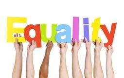 Разнообразные люди держа равность слова стоковое изображение rf