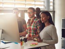4 разнообразных работника стоя рядом с компьютером Стоковые Фотографии RF