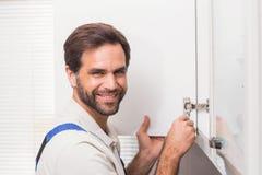 Разнорабочий исправляя кухонный шкаф стоковое изображение rf