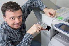 Разнорабочий исправляя принтер офиса или машина экземпляра Стоковые Фото