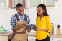 Разнорабочий и женщина смотря доску сзажимом для бумаги Стоковая Фотография RF