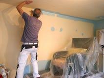 Разнорабочий, который штрихует стену с крася роликом стоковые изображения rf