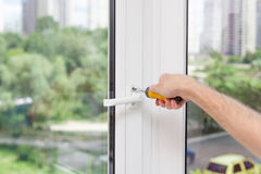 Разнорабочий ремонтирует пластичное окно с отверткой стоковое изображение rf