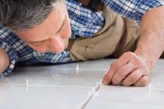 Разнорабочий устанавливая прокладки между плитками Стоковые Фото