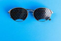 Разный вид 2 стекел на голубой предпосылке МЕДИЦИНСКАЯ принципиальная схема Взгляд сверху Eyeglasses Pinhole черные помогают расс стоковая фотография rf