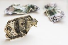 Разобранные 100 и 50 долларов на белой предпосылке Стоковые Изображения
