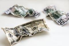Разобранные 100 и 50 долларов на белой предпосылке Стоковая Фотография