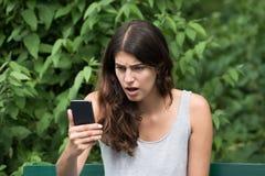 Разочарованная женщина смотря мобильный телефон Стоковое Изображение RF