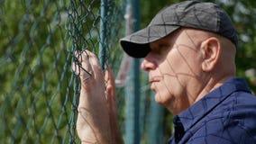 Разочарованная задняя часть человека металлического пребывания загородки грустного и безвыходного стоковая фотография rf