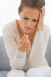Разочарованная молодая женщина смотря на пилюльке Стоковые Фото