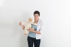 Разочарованная привлекательная молодая женщина сдерживая игрушку или плюшевый медвежонка с клубком и хмурый взгляд плюша гнева Стоковое Изображение