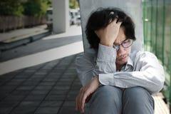 Разочарованная усиленная голова молодого азиатского человека касающая и чувствовать разочарованный или вымотанный Безработная кон Стоковые Фотографии RF