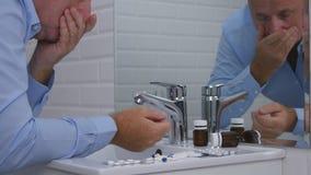 Разочарованное изображение человека в Bathroom с таблетками и лекарствами на раковине стоковые фотографии rf