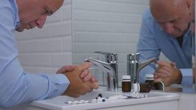 Разочарованное изображение человека в Bathroom с таблетками и лекарствами на раковине стоковые изображения