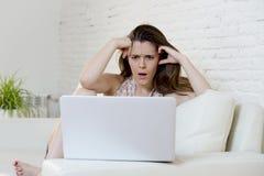 Разочарованное кресло девушки дома используя интернет для изучать с портативным компьютером Стоковые Фотографии RF