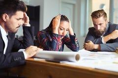Разочарованные бизнесмены сидя на таблице в офисе, споря пока обсуждающ проект Стоковые Изображения