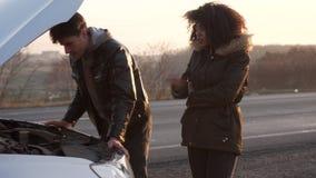 Разочарованные пары с открытым клобуком сломленного автомобиля на обочине сток-видео
