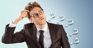 Разочарованный бизнесмен против голубых предпосылки и вопросительных знаков Стоковое Изображение RF